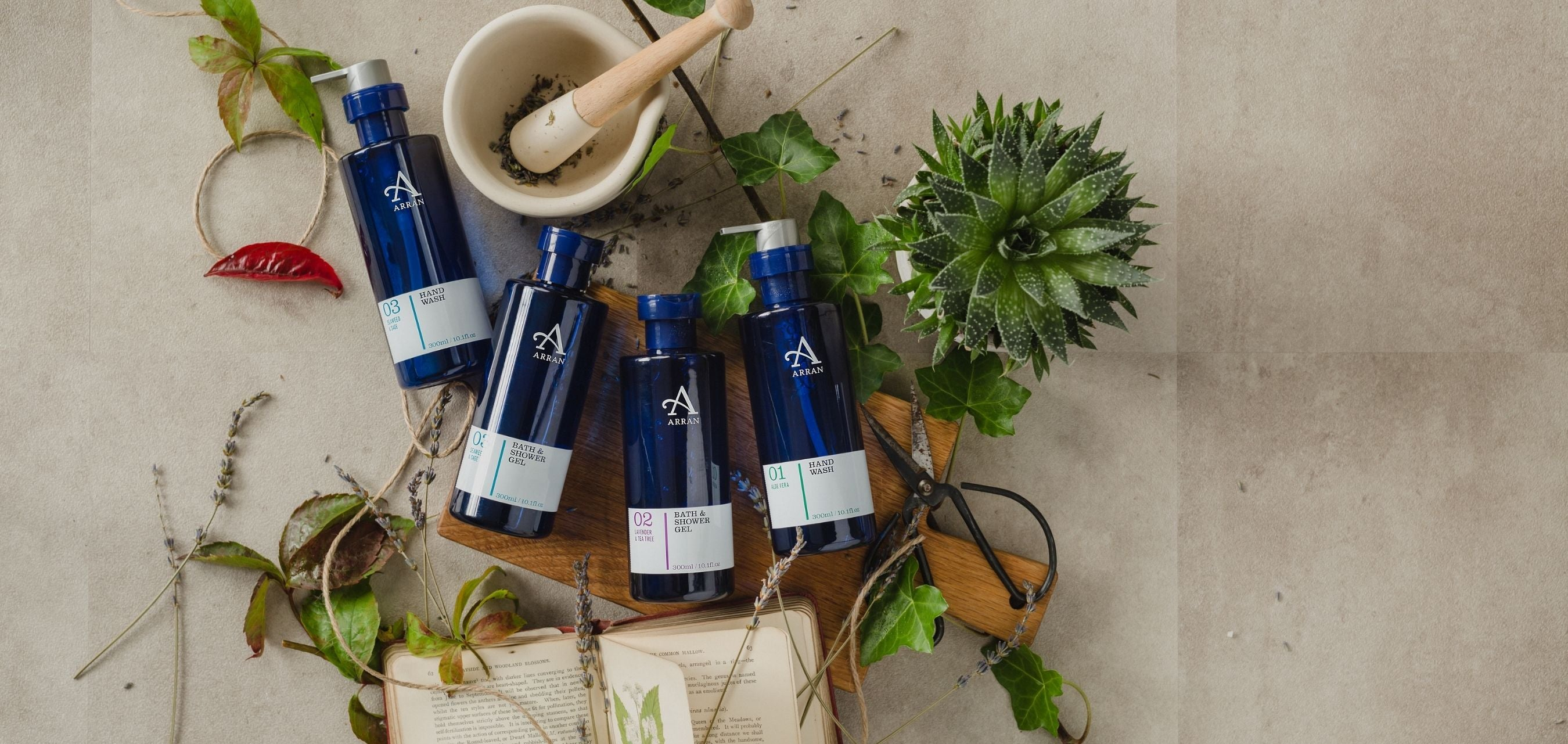 Assorted blue-bottled Hand Washes and Shower Gels with apothecary books.