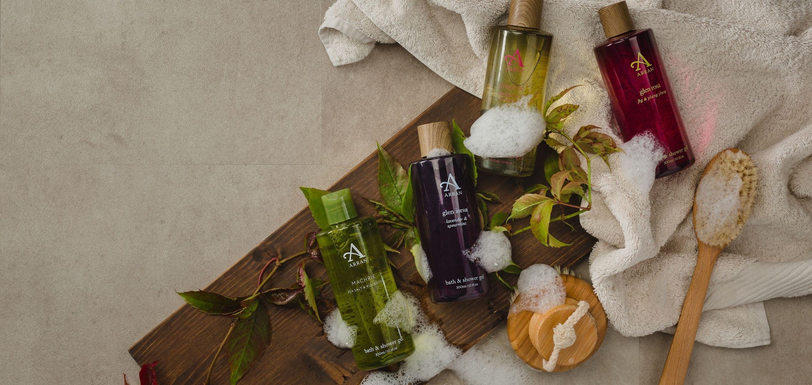 Four shower gels placed on dark wooden plank with light pink towel and body brush.