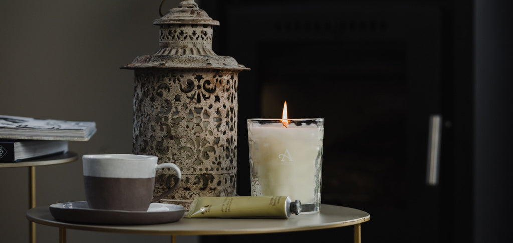 Glowing scented candle and miniature hand cream tube, placed on table with mug of coffee and decorative lantern in background.