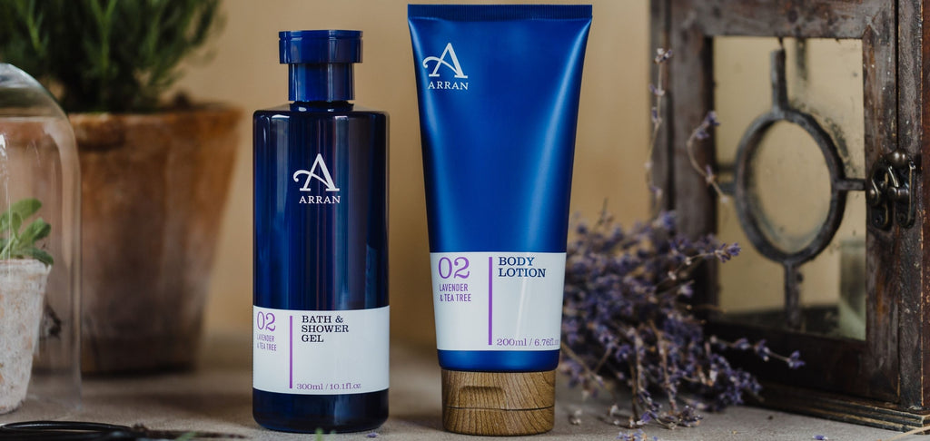 Blue Shower Gel bottle and Body Lotion tube with vintage lantern and rustic plant pot in background.