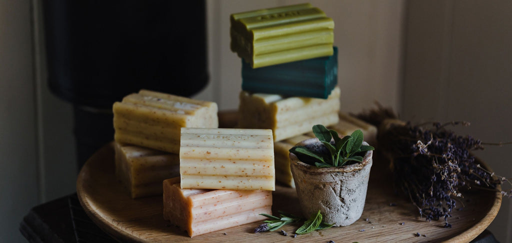 Stack of soaps placed on wooden dish with small plant pot.