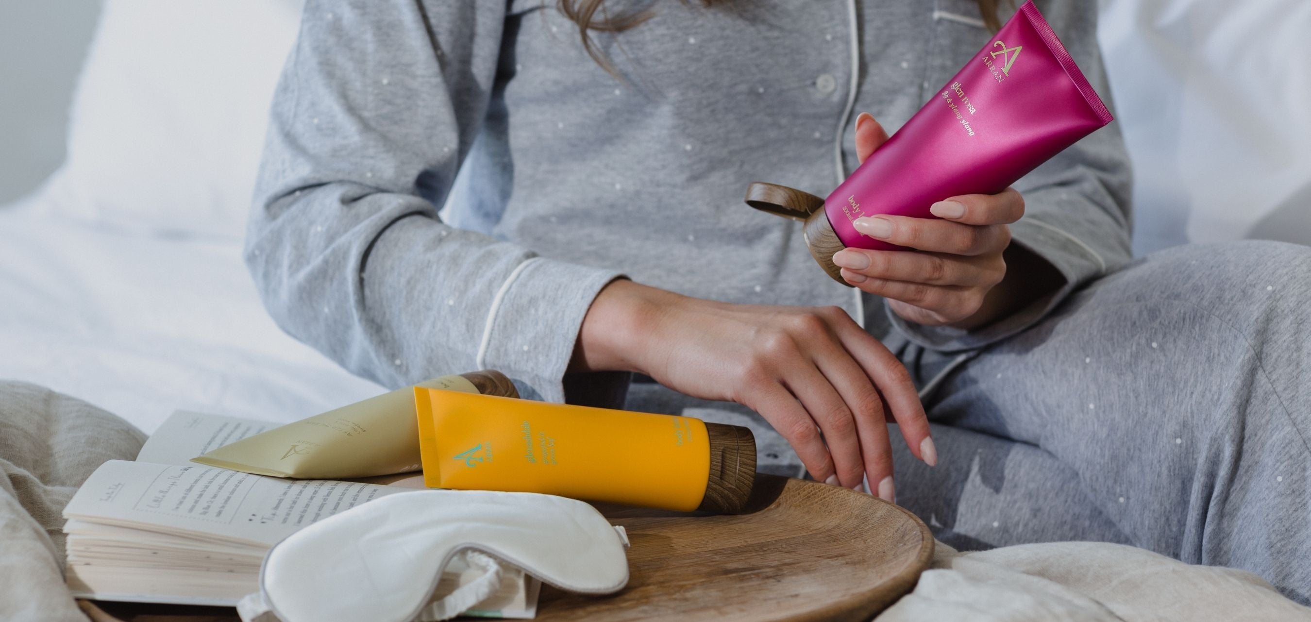 Image of woman in bed applying Body Lotion to hand.