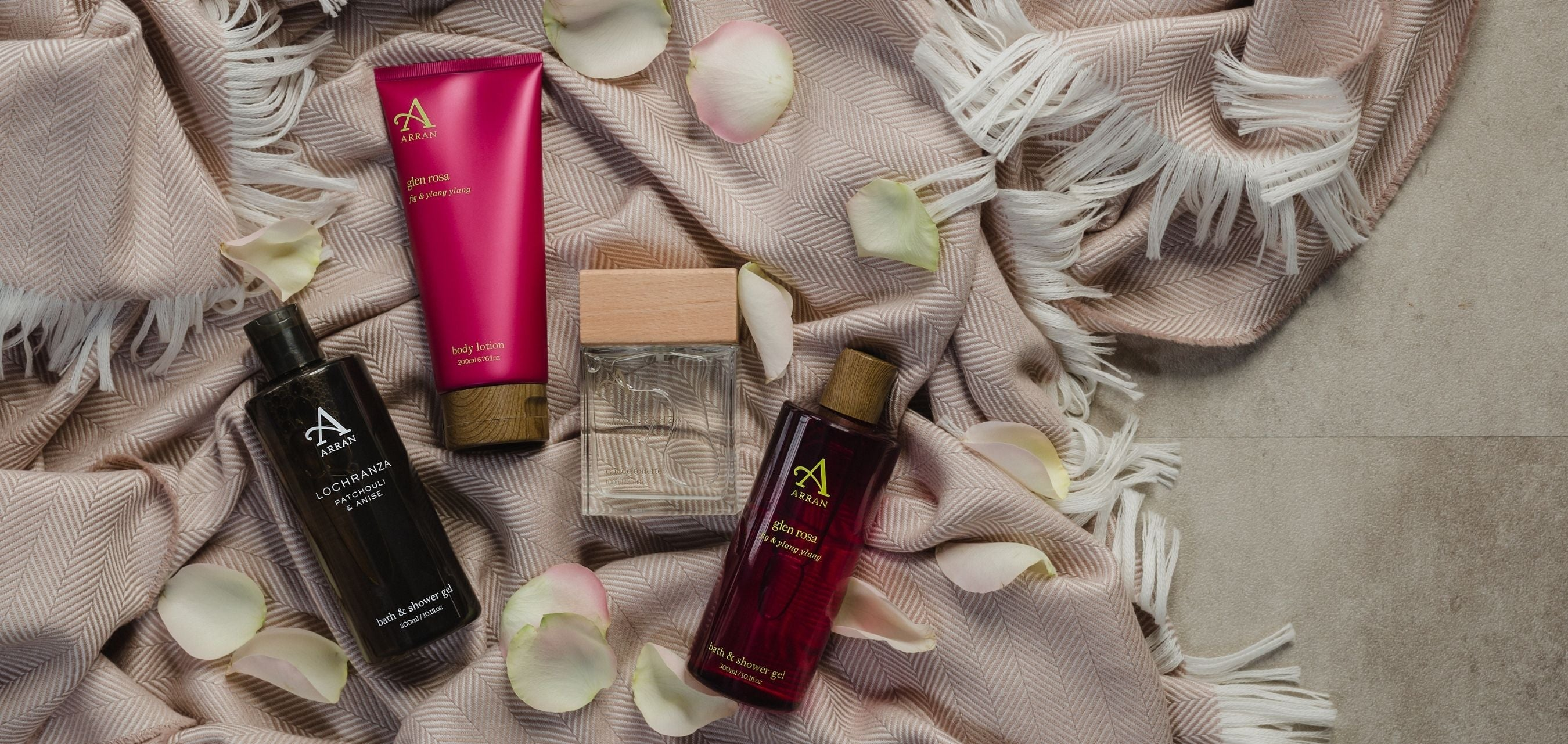 Men's shower gel and aftershave and women's body lotion and shower gel, placed on pale pink blanket surrounded with white rose petals.