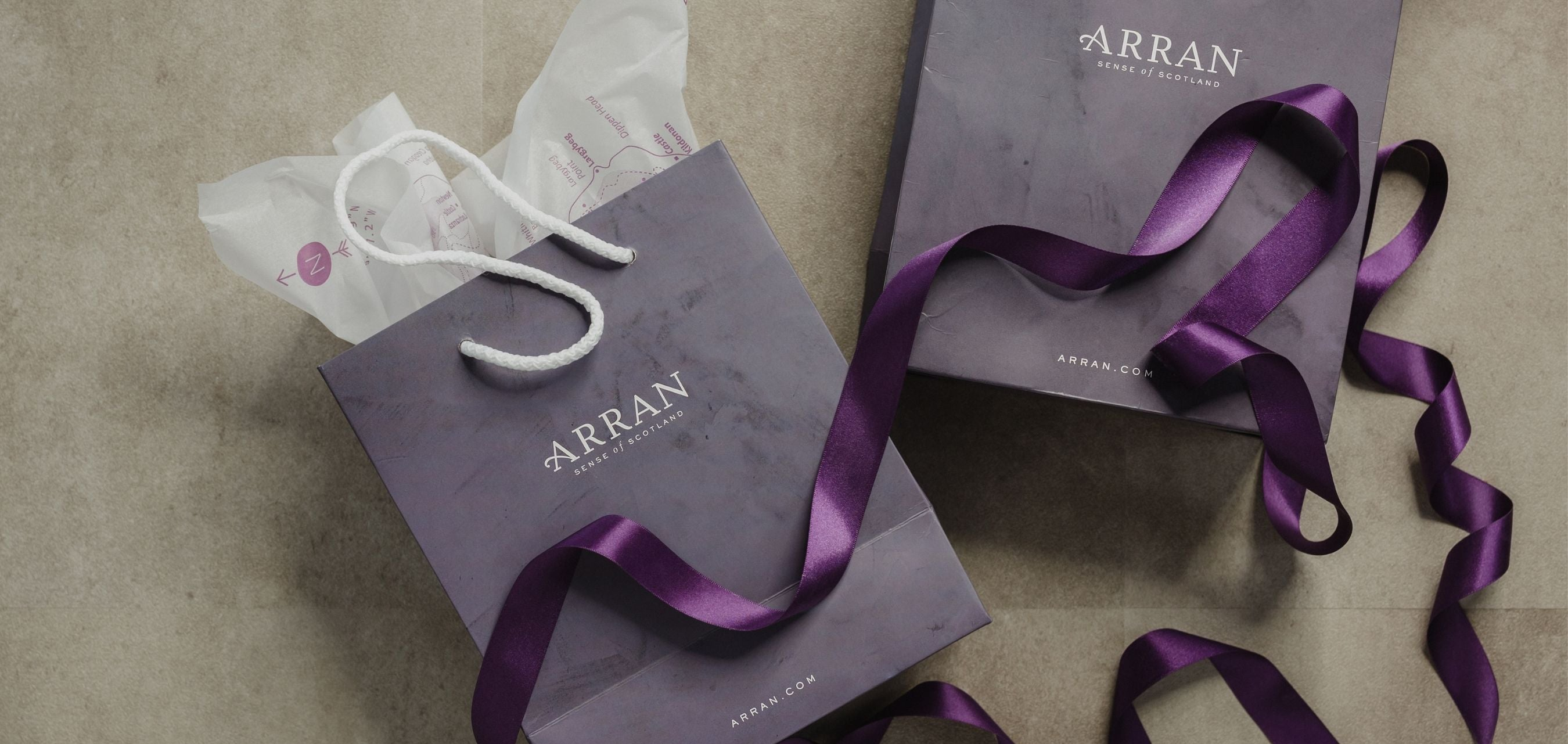 Two purple gift bags filled with white tissue paper and dark purple ribbon.