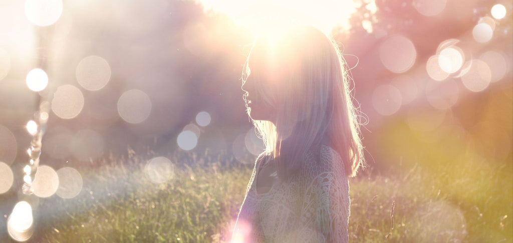 Image of girl standing in garden, with a golden sunrise in the background.