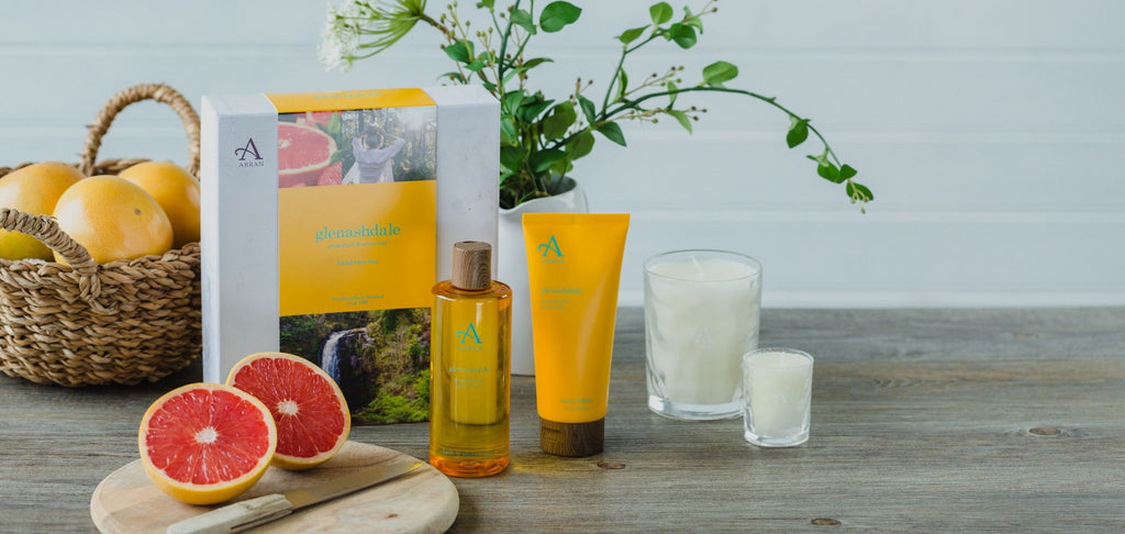 Image of citrus shower gel, body lotion and candles on wooden table with sliced grapefruits in background