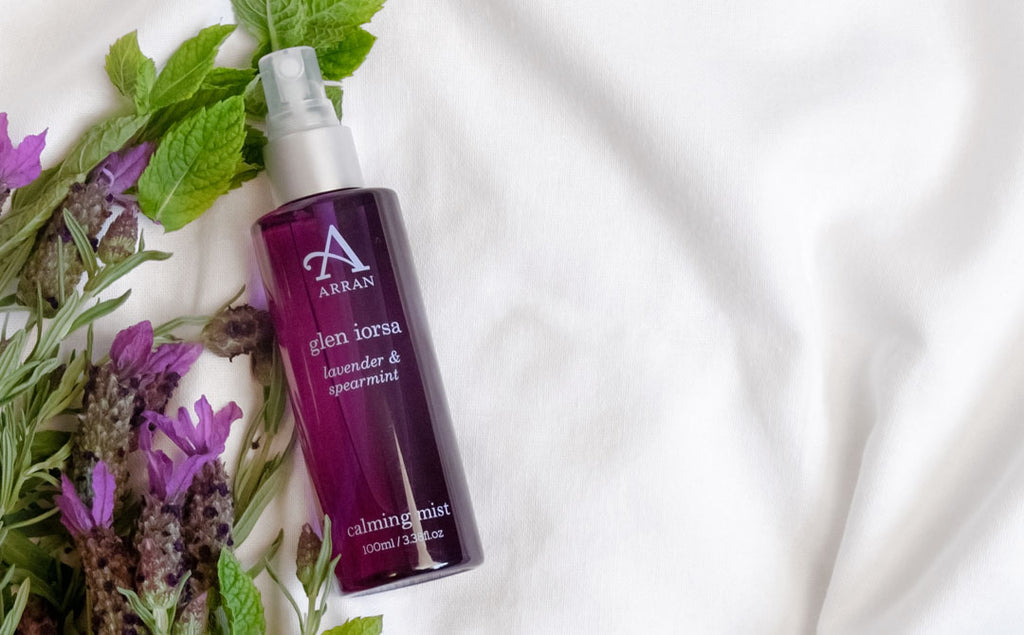 Purple bottle of lavender pillow mist, placed on white bed sheet with extracts of lavender and spearmint.