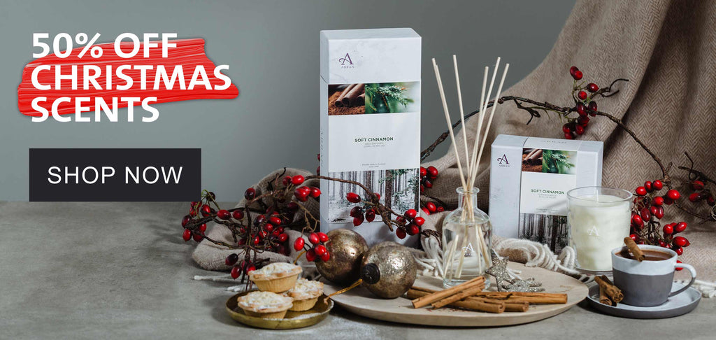 """Candle and Reed Diffuser on table with gold dish, cinnamon sticks and beige blankets featuring text to say """"50% off Christmas Scents. Shop Now"""""""