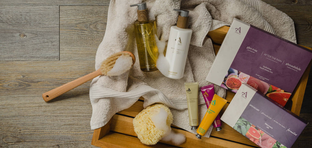 Image of a hand wash and hand cream with beige towel, body brush and natural loofah sponge