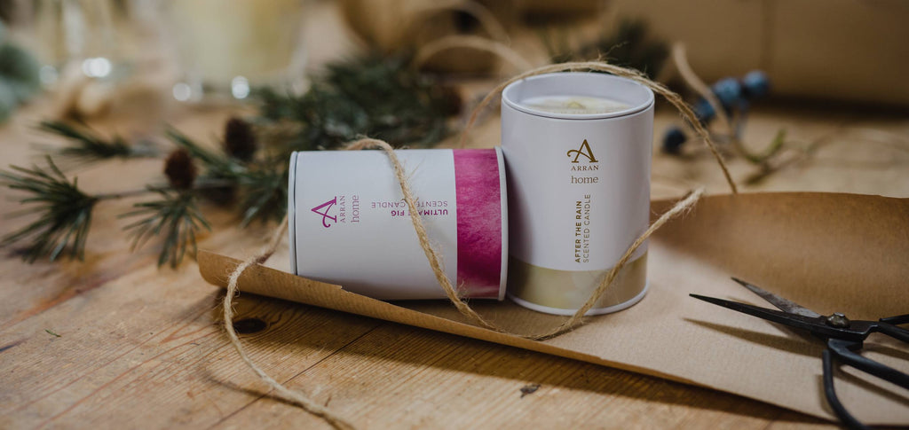 Image of two scented candles in tins, with twine, scissors and kraft wrapping paper in the background.