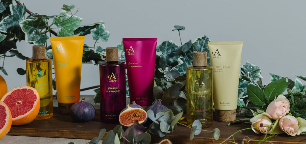 Image of three shower gels and body lotions, placed on dark wooden plank with green foliage, grapefruit slices, rose petals and sliced figs