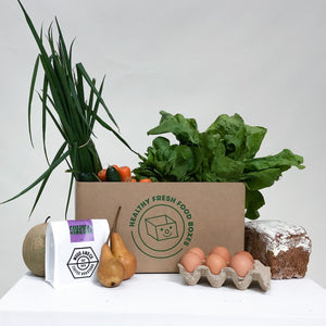 The Healthy Box includes 6 vegetables, 2 fruits, freshly baked bread, half a dozen eggs, and a Grocery Surprise. The box pictured is packed with spring onions, carrots, zucchinis, pears, and a melon. The Grocery Surprise shown is a bag of premium coffee beans from Wood and Co Coffee Roasters. All produced included were sourced organically and from local Australian businesses.