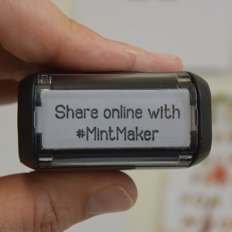 Top of a self inking stamp that reads 'Share online with #MintMaker'