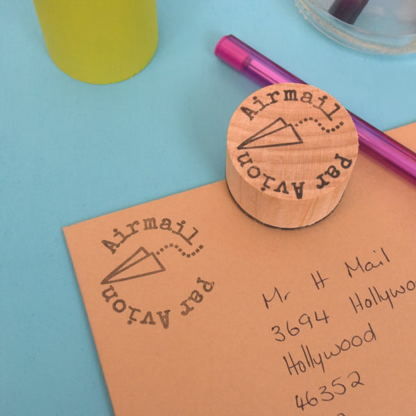 Airmail and Par Avion Rubber stamp with a paper plane on an addressed envelope.