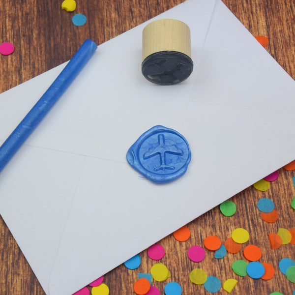 Airplane wax seal on an envelope with wax seal stamp lying nearby