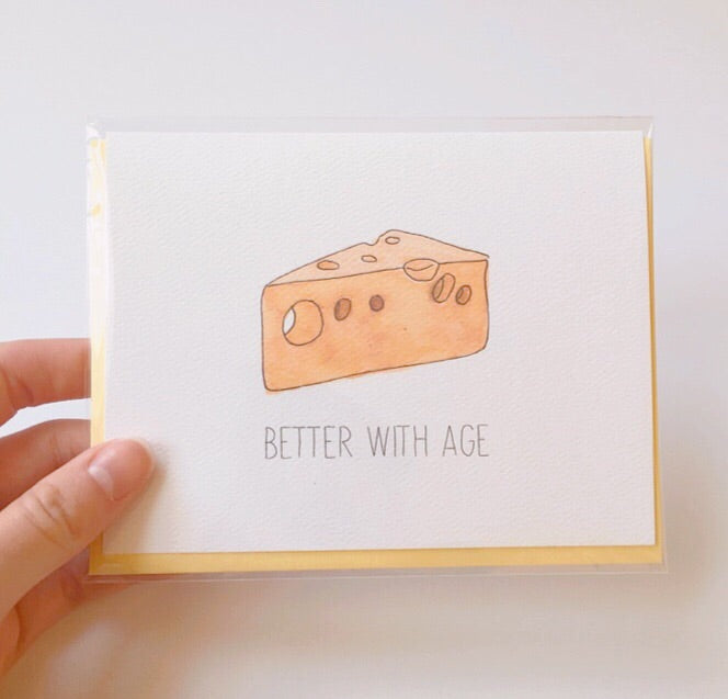 "Cute birthday card featuring a watercolor wedge of swiss cheese and the pun ""better with age"" 