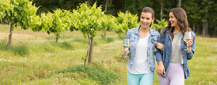 Women walking through field with wine glasses