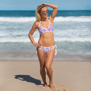 Woman holding her head on the beach wearing floral bikini and sunglasses