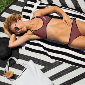 Woman holding her head laying on black and white beach towel in the grass wearing ruby red Axel Grayson bikini and sunglasses