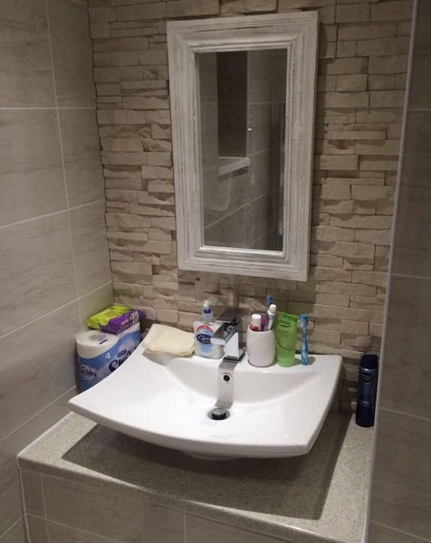 Cream Stone Split Face Tiles Used Around A Bathroom Mirror