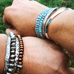 Beaded and silver cuffs on woman's wrist