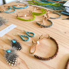 copper beads, feathers, and turquoise on a wooden table