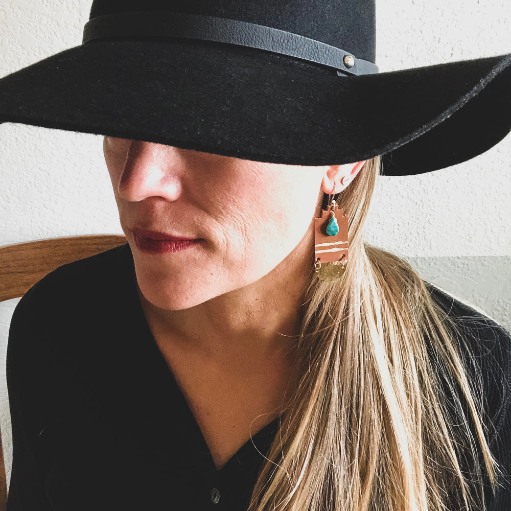 woman with black cowgirl hat wearing leather earrings