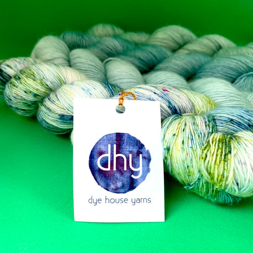 Dye House Yarns Merino Linen Blend, Artistic shot 4 green skeins and logo