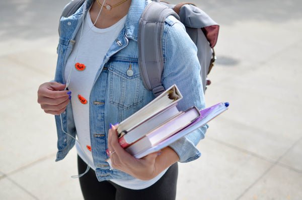 Student carrying books and grey backpack, wearing a pale wash denim jacket paired with a white t-shirt.