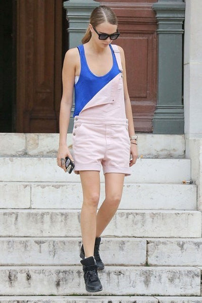 Woman walking down steps wearing pale pink dungaree shorts with half-open bib revealing blue vest.