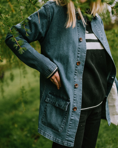 Midriff view of model wearing Vera Organic Workwear Jacket from WASH CLothing Company with clear view of corozo buttons, revealing 'Oui' Organic Hoodie in Navy underneath.