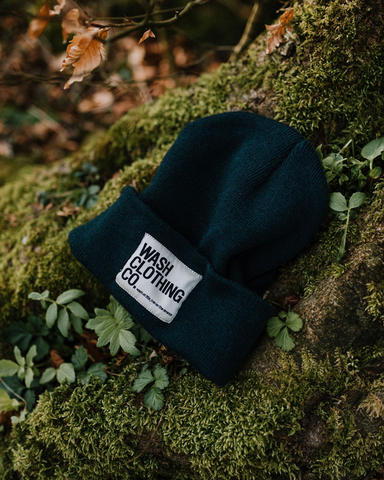 Close-up view of Sinead Navy-Blue Cuffed Beanie on bed of moss.