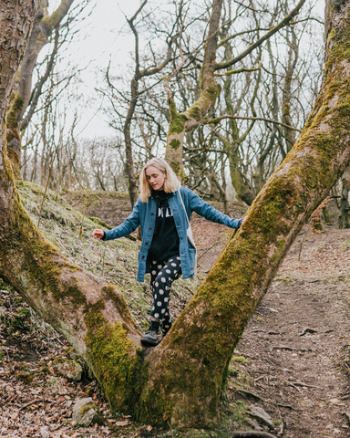 Model in countryside stepping through the 'v' of a tree branch wearing garments from WASH clothing company.