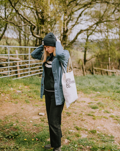 Model standing in the curner of field, adjusting 'Sinead' Cuffed Beanie in Navy.