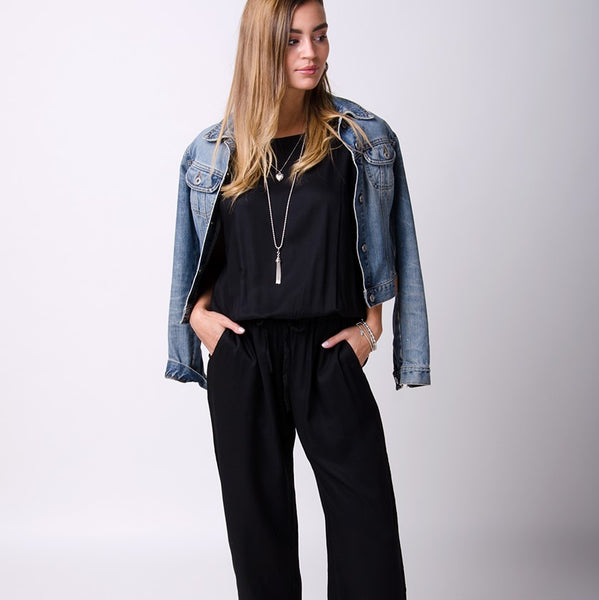 Black relaxed fit jumpsuit with hands in front pockets and mid-wash denim jacket draped over shoulders.