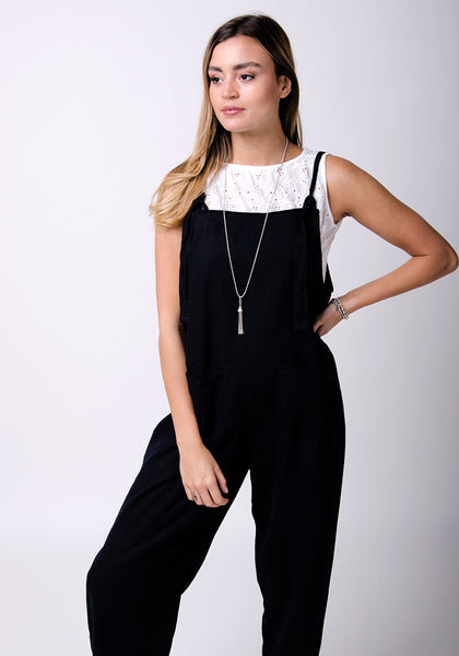 Wearing black dungarees with hand on left hip paired with white top.