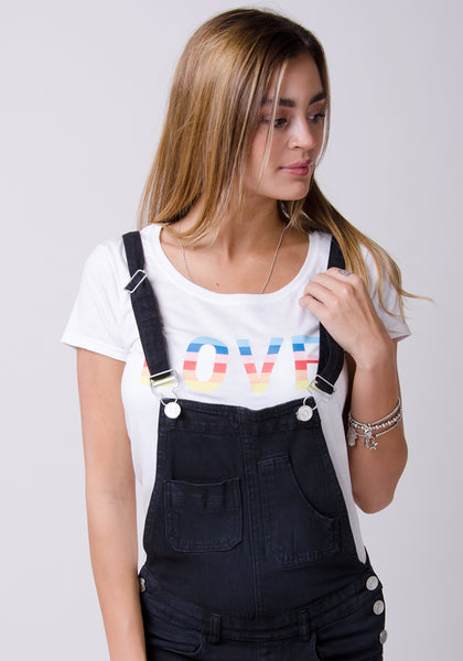 Top-half shot of model wearing dark dungarees and holding left strap. Paired with white t-shirt.