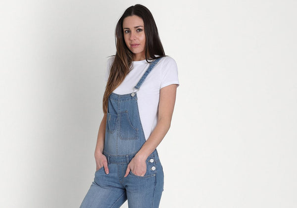 Wearing mid wash women's dungarees with hands in front pockets. Paired with white t-shirt.