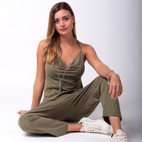 Sitting on floor  wearing Jools-style khaki-olive jumpsuit.