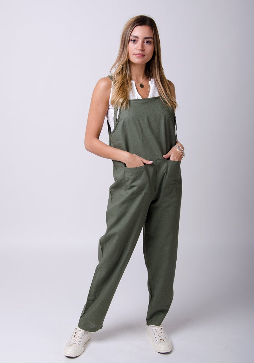 Full frontal pose with hands in front pockets, looking to her left, wearing green bib-overalls.