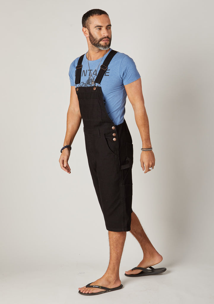 Two-thirds pose focussing on front pockets, side buttons and adjustable straps of men's black dungaree shorts.