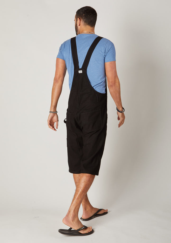 Rear full-length pose men's black bib-overall shorts showing back pockets