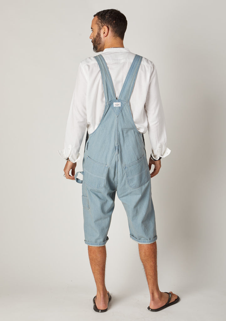 Rear full-length pose men's denim bib-overall shorts showing back pockets and Wash Clothing logo label.