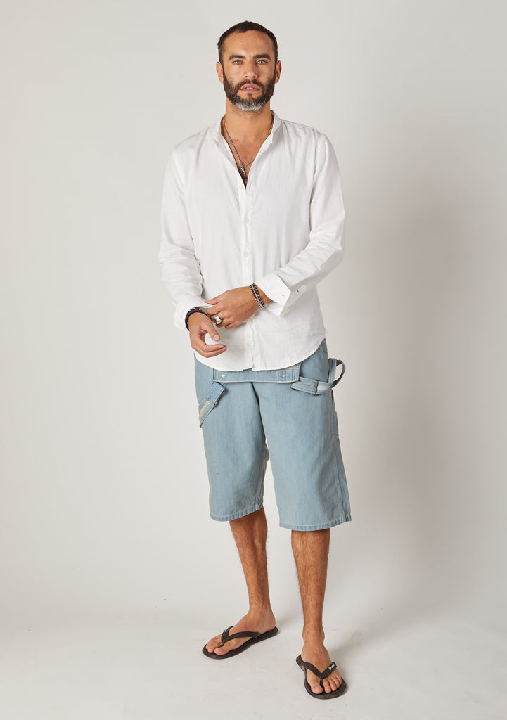 Front full-length pose of men's pale blue denim overall shorts styled with bib down.