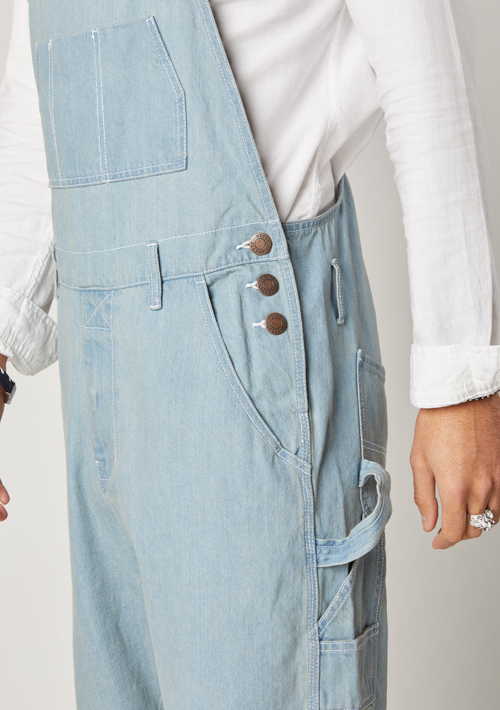 Close-up of Chet Pale Blue Denim Bib and Brace shorts for men showing the side button fastening and hammer loop.