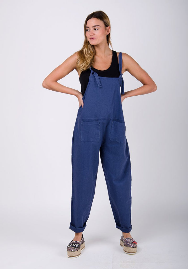 Full-frontal pose with hands on hips, looking to her right. Wearing practical, Roxanne-style linen dungarees.