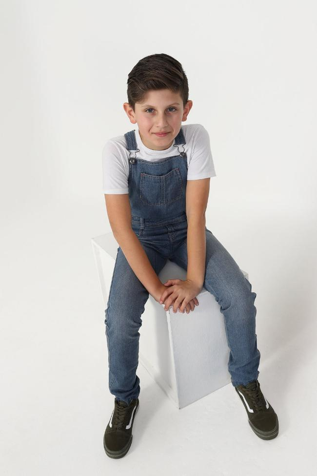 Full frontal of boy sitting on box wearing stylish kids bib-overalls.