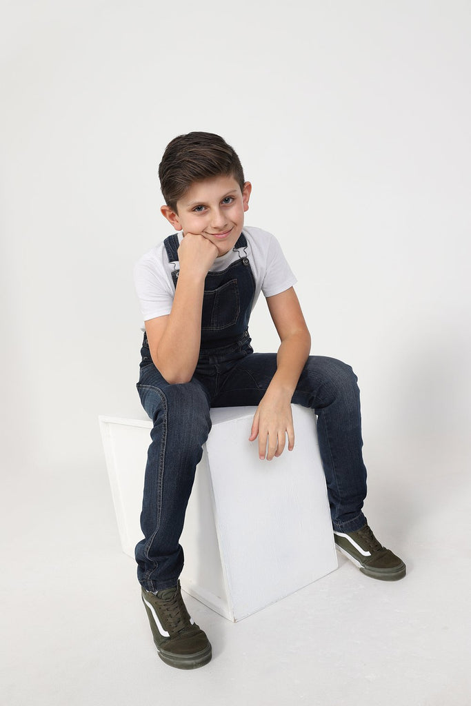 Boy slouching on box, wearing durable zip fly, machine washable kids overalls.