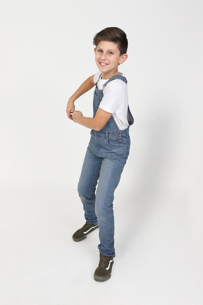 Full length side-view active pose of boy wearing durable slim-fit overalls.