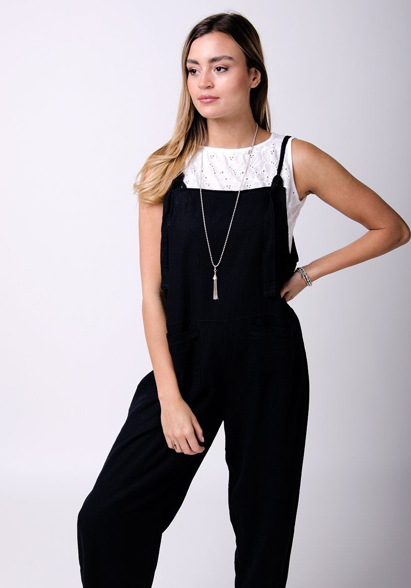 Two-thirds pose with left hand on hip, wearing basic linen, dungaree style jumpsuit.